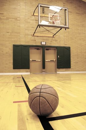 swish: Basketball on court with hoop in the background