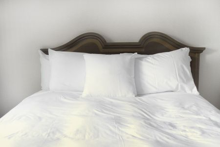 red pillows: Group of several white pillows on a bed with headboard