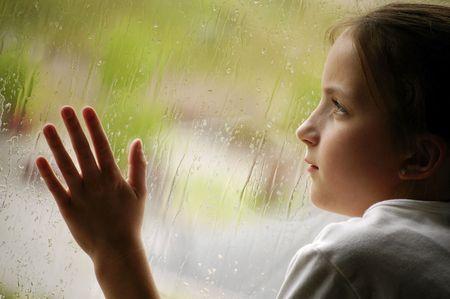 雨の日窓の外を見て女の子