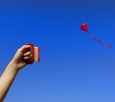 papalote: Chica que volaba una cometa en un parque con el cielo azul Foto de archivo