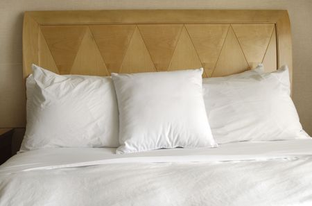 kingsize: Group of several white pillows on a bed with headboard