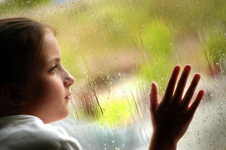 lloviendo: Chica busca a cabo en la ventana un día lluvioso