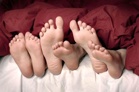 Verschillende voeten poking uit dekens op bed