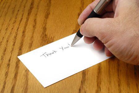 persona escribiendo: Persona de la escritura gracias nota con bol�grafo en la tarjeta Foto de archivo