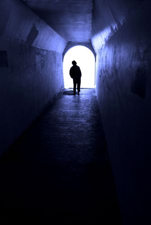 Person in long tunnel walking towards the light Stock Photo