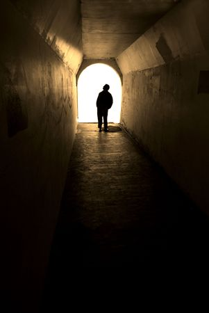 Person in long tunnel walkway with white light at the end Stock Photo