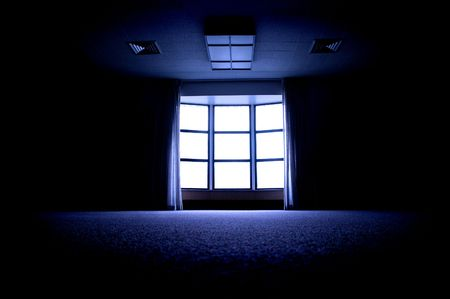 Large dark room with bright light coming in through paned window