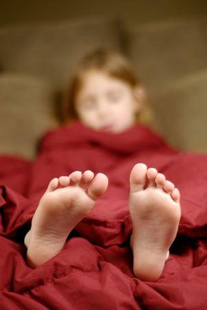Meisje slapen met voeten poking uit dekens