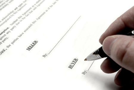 Hand holding pen signing a purchase contract or agreement photo