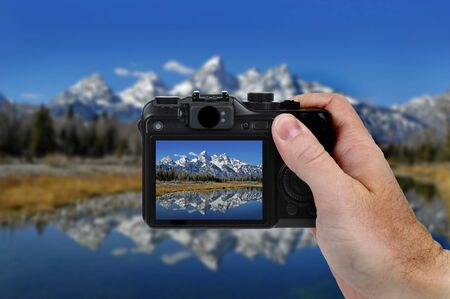Hand holding camera taking a picture of Teton Mountains and River photo