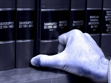 multiples: Close up of hand pulling out a law book on bankruptcy Stock Photo