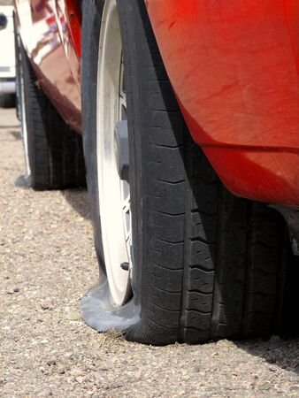 flat tyre: Car with two flat tires on paved road