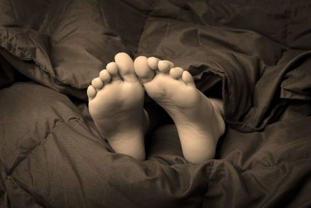 big foot: One person sleeping with feet poking out of blankets Stock Photo