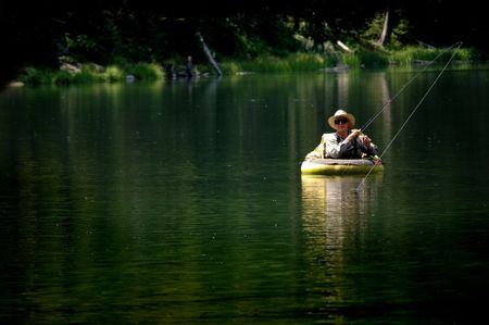 Man flyfishing in lake in a float tube photo