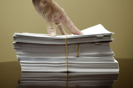 pile reuse: Hand on top of stack of business papers with rubber band