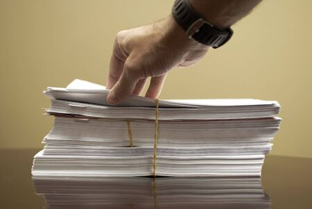 Hand on top of stack of business papers with rubber band photo