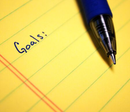 Goals written on yellow paper with blue pen Imagens