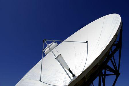 Satellite transmission dish against blue sky photo