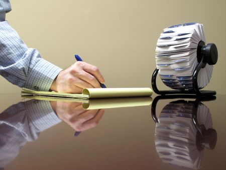 rolodex: Hand holding pen writing on a pad of paper