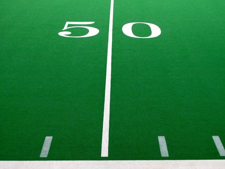 Football field with green turf and white yardlines and markers                        photo
