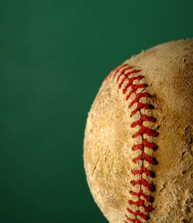 Old worn baseball isolated with green background photo