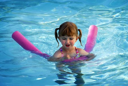 Young girl swimming in swimming pool with wet hair photo