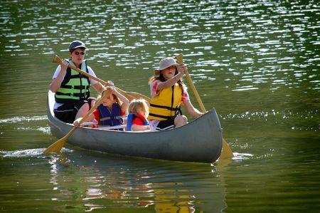 piragua: Familia en una canoa a orillas de un lago en el verano