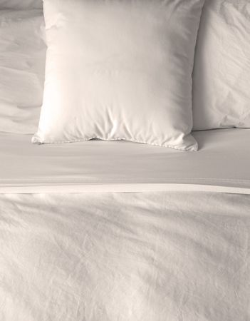 Group of several white pillows on a bed with headboard photo