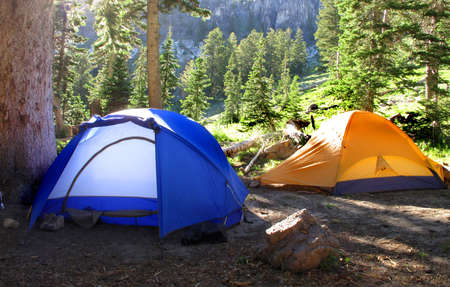 roughing: Camp tents with forest and mountains in the background
