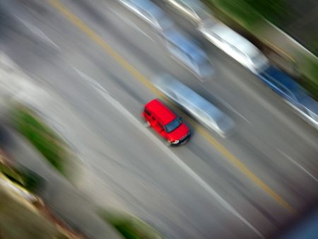 Red Car driving along road with blurred background photo