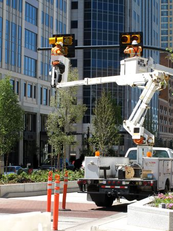 strapped: Men working on traffic lights changing bulbs Stock Photo