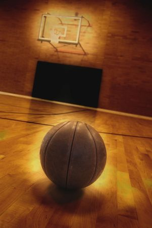Basketball on floor of empty basketball court photo