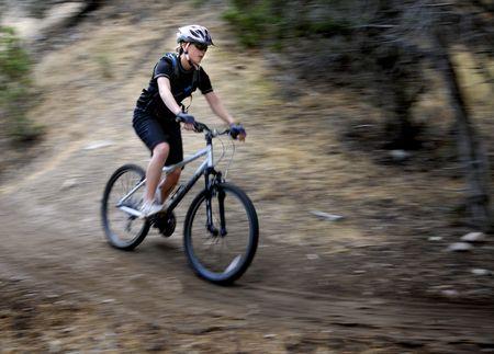 Young Woman Riding Mountain Bike in Wilderness photo