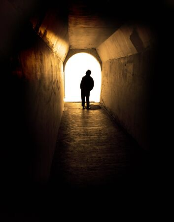 1 person: Person in long tunnel walkway with white light at the end Stock Photo
