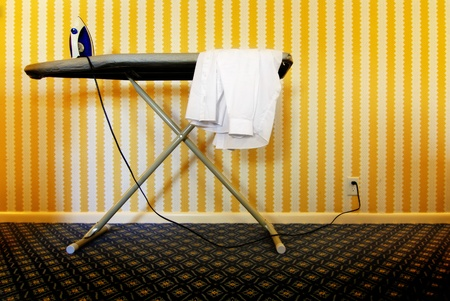 Ironing board with shirt and iron against wall