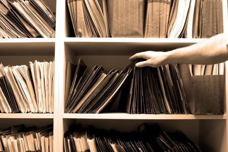 Hombre buscando archivos en plataforma en una sala de archivo