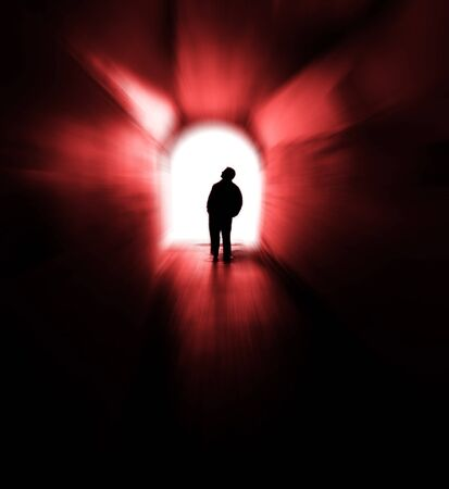 Person in long tunnel walkway with white light at the end Banco de Imagens
