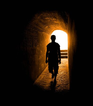 lighten: Person in long tunnel walkway with white light at the end Stock Photo