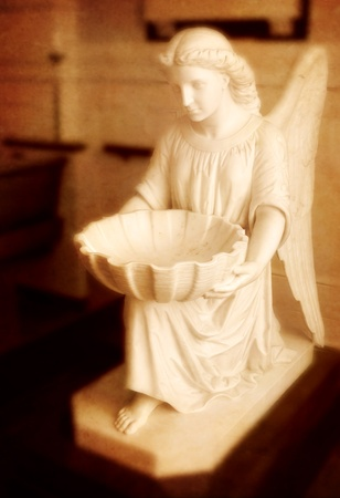 Statue of Angel with hands outstretched holding a basin photo