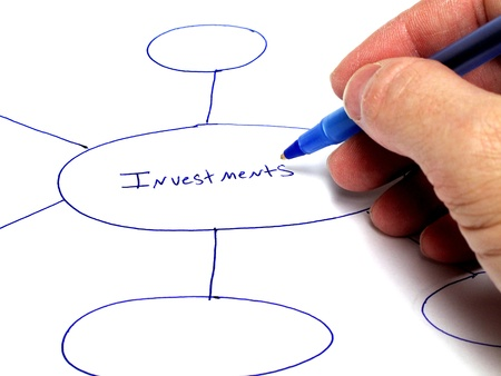 Person writing notes on paper about plans for investments Stock Photo