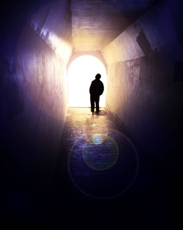 darkness: Person in long tunnel walkway with white light at the end Stock Photo