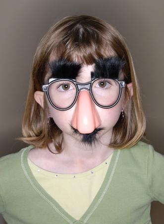 재미 있은 코와 안경 마스크 얼굴에 어린 소녀