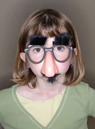 Little girl with funny nose and glasses mask on face photo
