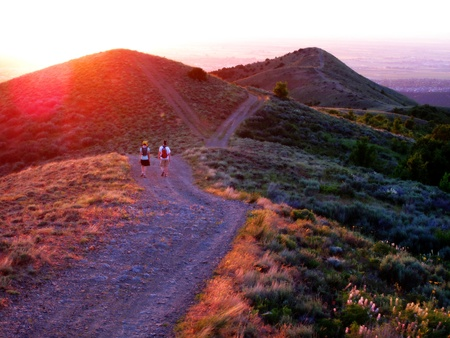 Travel Backpack: Ni�as caminatas a lo largo de una monta�a en el amanecer o el atardecer
