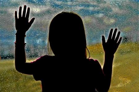 Meisje kijkt uit raam op een regenachtige dag