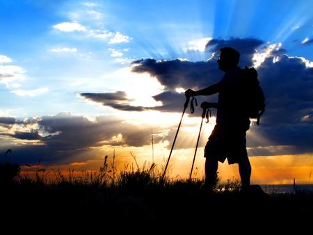 Man Wandern auf einen Berg bei Sonnenuntergang oder Sonnenaufgang