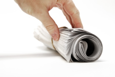Rolled up newspaper isolated on white background with hand reaching photo