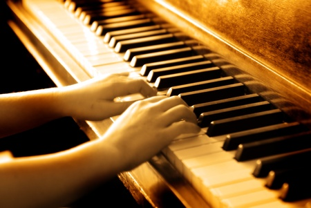 transcription: Small hands playing piano keys with wood grain and sepia tone