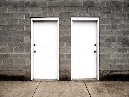 fermer la porte: Deux portes blanches sur le mur de brique illustrant les choix