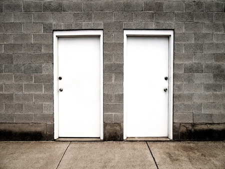 Two white doors on brick wall illustrating choices